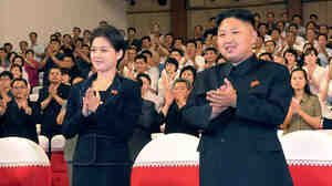 In this photo released by the Korean Central News Agency (KCNA) and distributed in Tokyo by the Korea News Service on Monday, July 9, 2012, North Korean leader Kim Jong Un, right, and a woman clap with others on Friday as they watch a performance by North Korea's new Moranbong band in Pyongyang. Now it appears they have gotten married.
