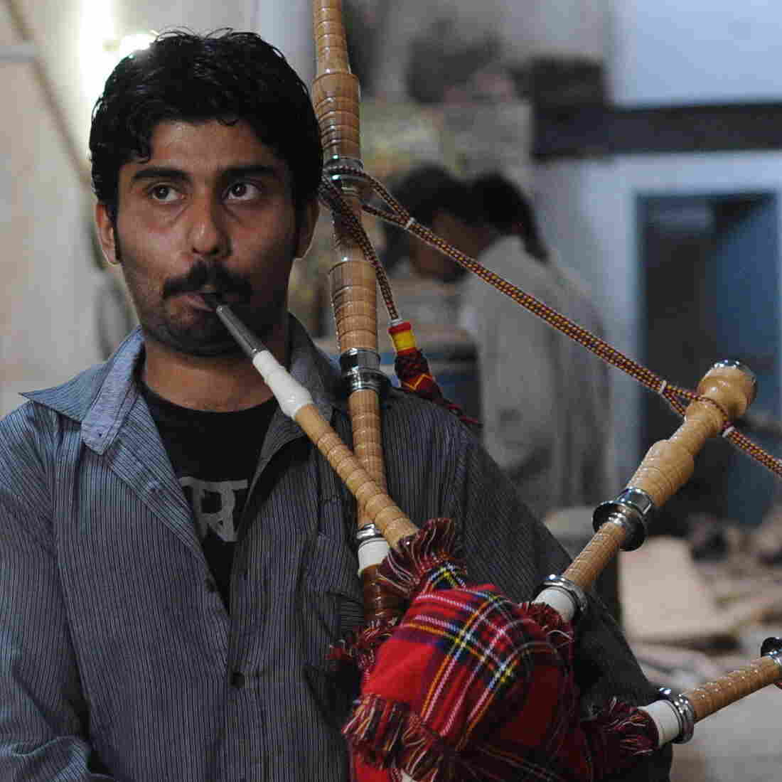 Ibrahim Ahmad, the son of the owner of the Imperial Bagpipe Manufacturing Co., tests a bagpipe at a factory in Sialkot, Pakistan. The Pakistani city is the largest producer of the instruments most commonly associated with Scotland.