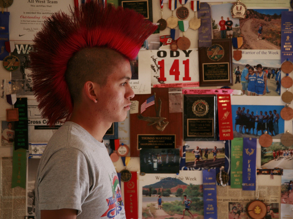 "Thomas Martinez stands in front of ""The Wall,"" an inspirational collection of his accolades, at his father's house."
