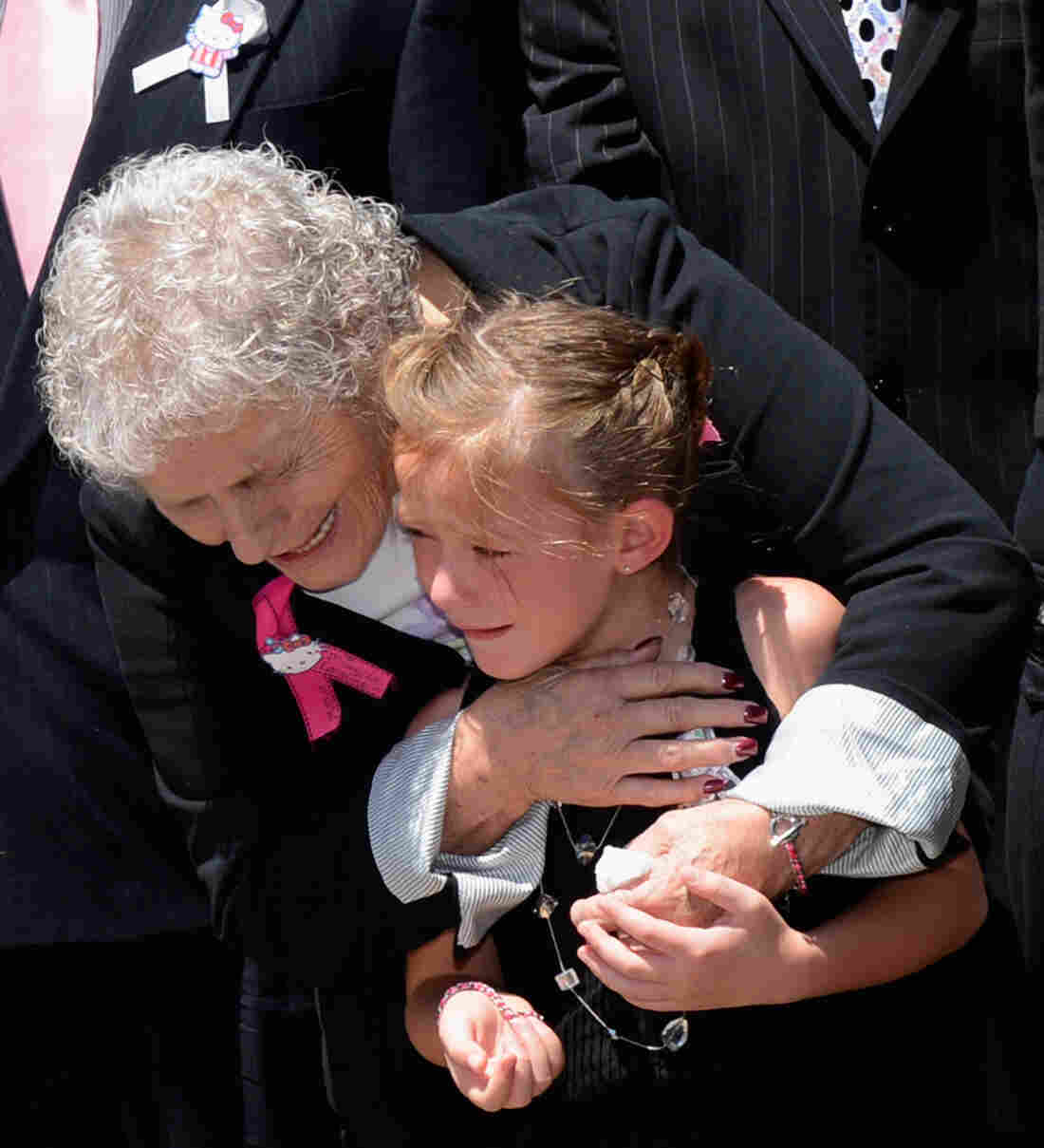 Grandma Marlene Kenobbe (L) comforts consoles Kailyn Vigil during Micayla Medek's funeral at the New Hope Baptist Church in Denver, Colorado.