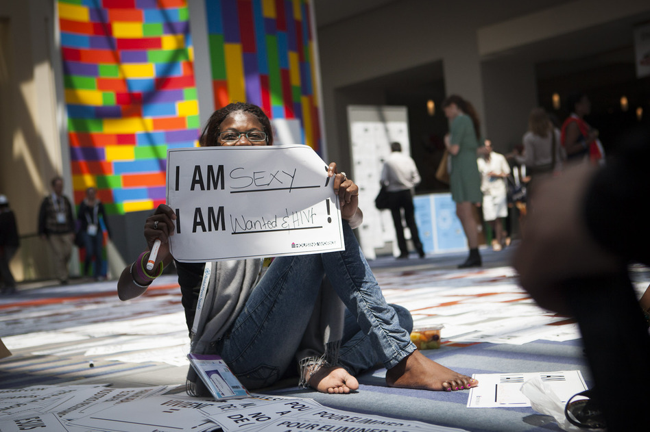 Getting the word out about HIV was a major goal of the Global Village. Helena Nangombe from Namibia holds up a sign written by her friend during a session that aimed to promote communication about HIV. (NPR)