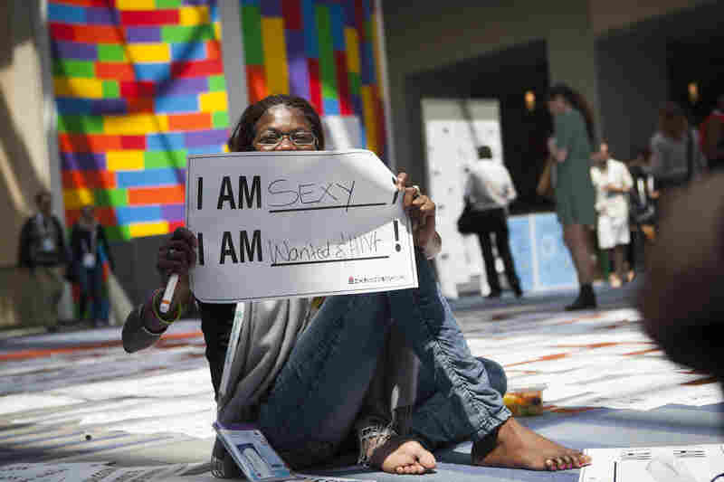 Getting the word out about HIV was a major goal of the Global Village. Helena Nangombe from Namibia holds up a sign written by her friend during a session that aimed to promote communication about HIV.
