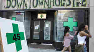 Pedestrians walk past a medical marijuana dispensary in the Echo Park area of Los Angeles Tuesday. The City Council voted that day to ban marijuana shops outright.