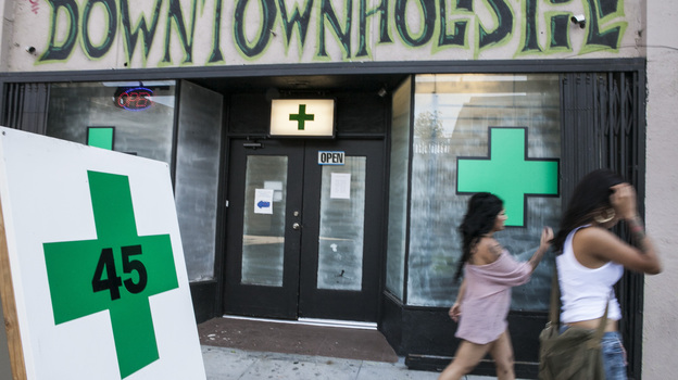 Pedestrians walk past a medical marijuana dispensary in the Echo Park area of Los Angeles Tuesday. The City Council voted that day to ban marijuana shops outright. (AP)