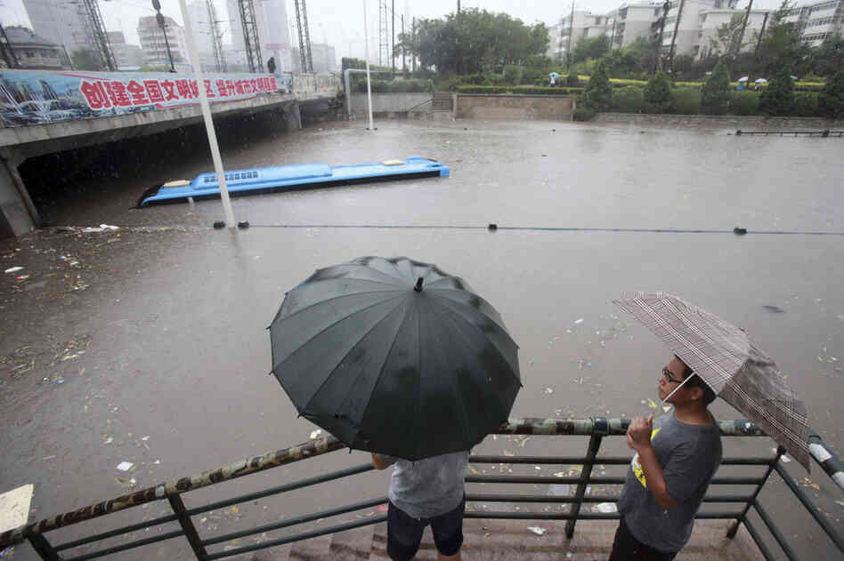 Residents look at a submerged bus on a flooded street in the Chinese city of Tianjin on Thursday. Beijing and neighboring areas have experienced the worst rainstorms in six decades. At least 77 people were killed, Chinese authorities said Thursday.