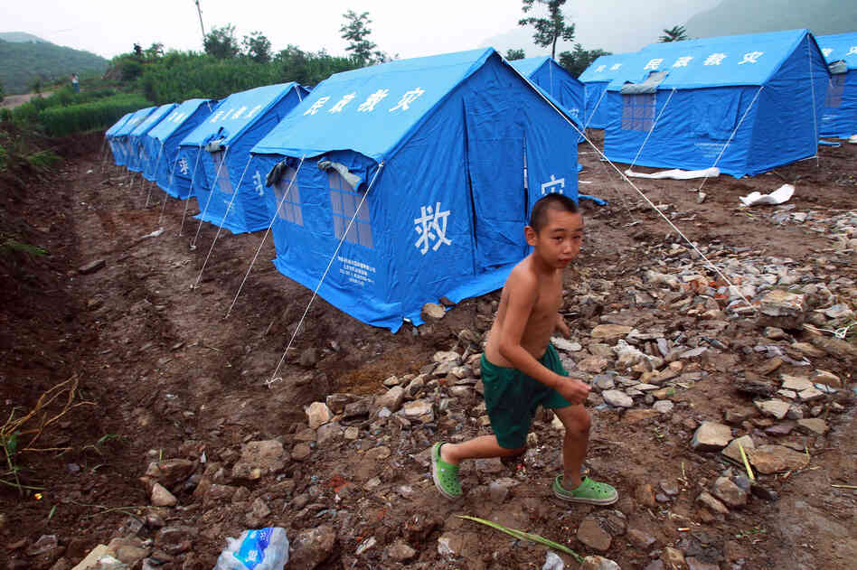 A young boy walks through a camp set up for victims of the flood in Beijing.