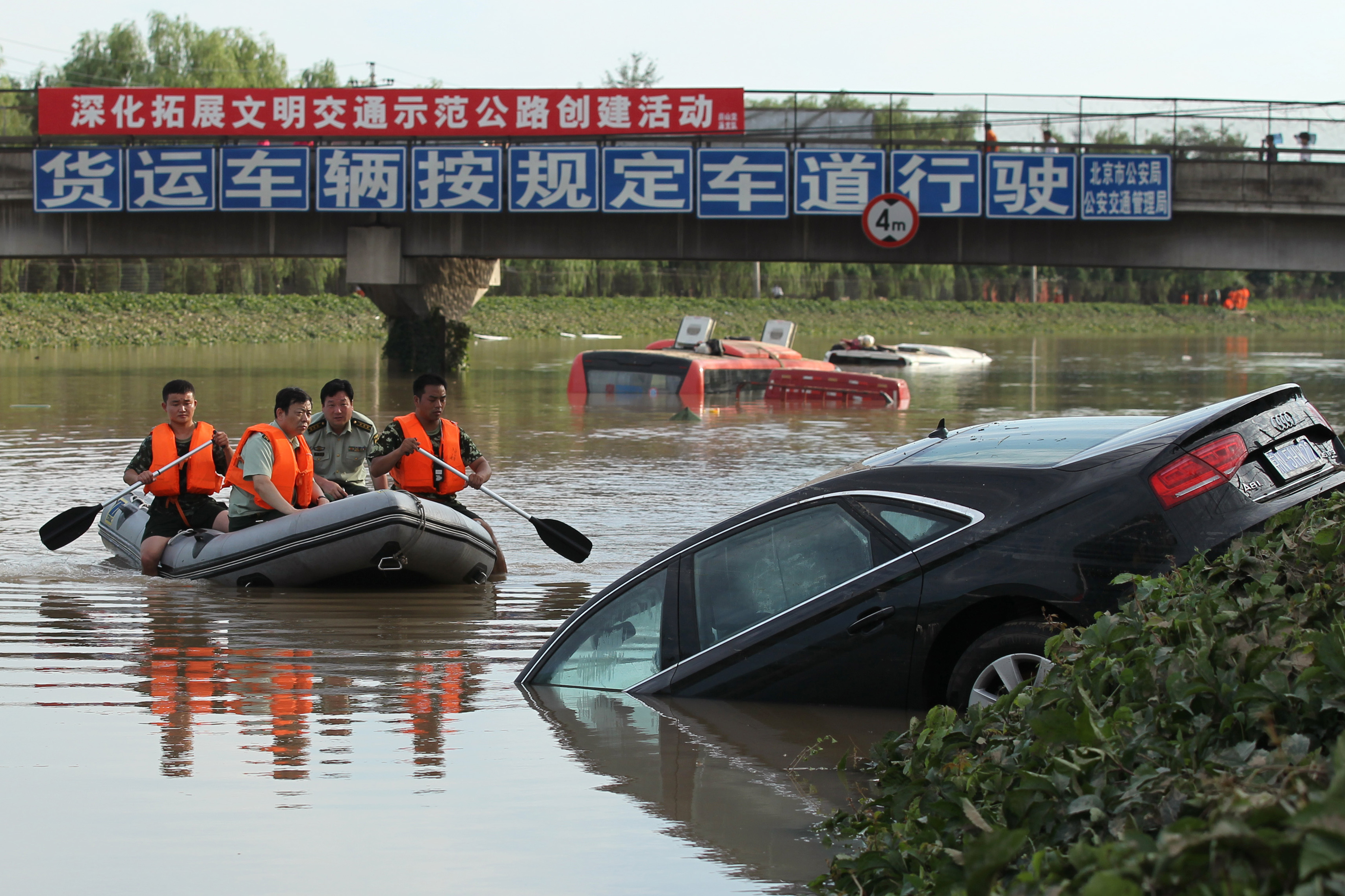 A rescue boat approaches a partially submerged car on a highway in the Fangshan District of Beijing.