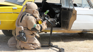 A student prepares an explosive charge to disarm a car bomb.