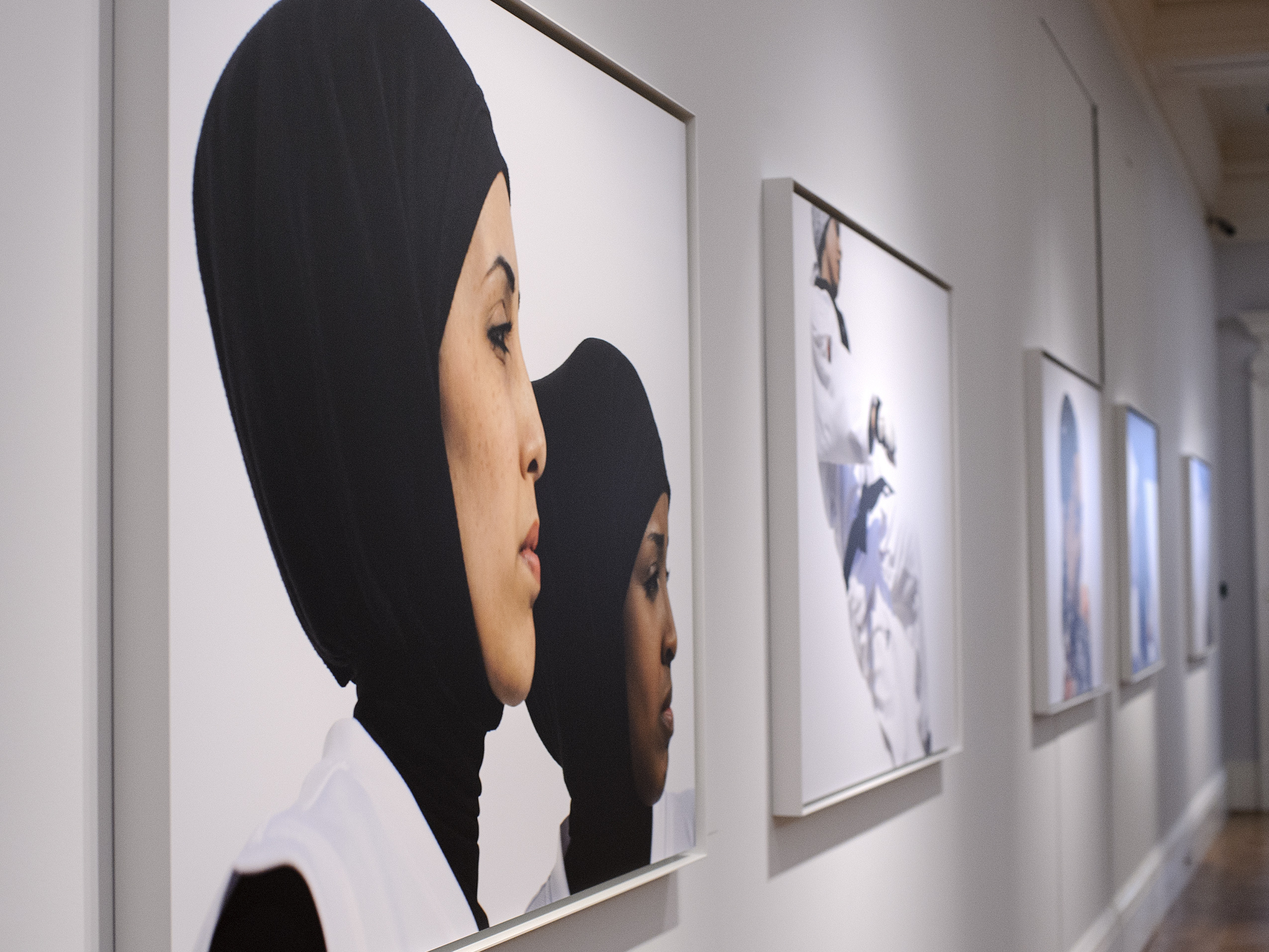 Photos hang at the opening of Hey'Ya Arab Women In Sport by Brigitte and Marian Lacombe at Sotheby's auction house in London.