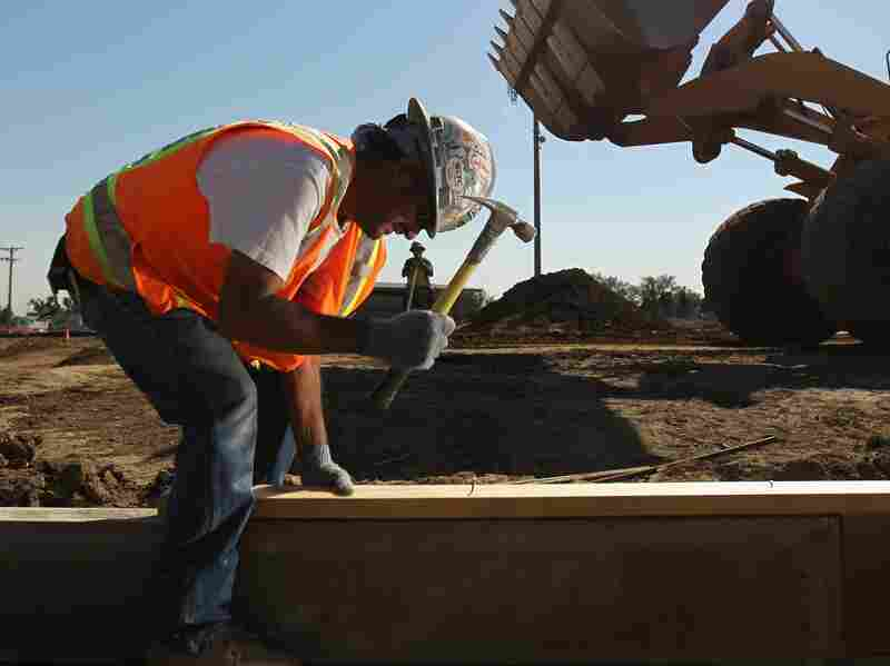 A worker at a Colorado National Guard construction site funded by federal stimulus funds in 2010 in Lakewood, Colo. Economists say the latest gross domestic product report shows the recession was less severe than previously thought. That's because government spending helped prop up the economy. Now, eyes are turning to the Federal Reserve to boost growth.