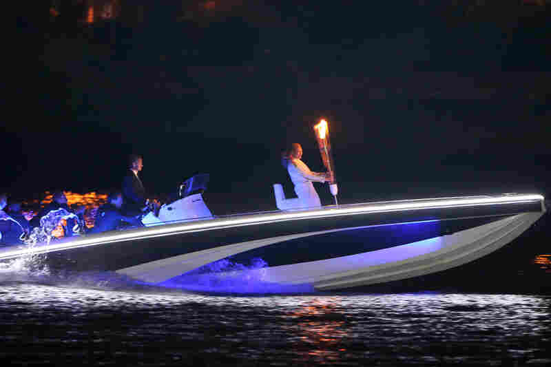 British soccer star David Beckham drives a speedboat carrying the Olympic flame to the opening ceremony.
