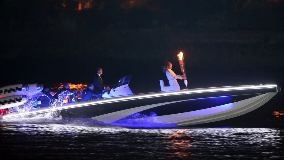 British soccer star David Beckham drives a speedboat carrying the Olympic flame to the opening ceremony. (Getty Images)