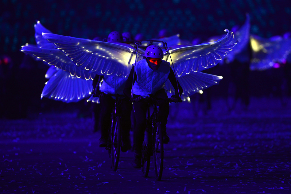 Winged performers ride bicycles during the opening ceremony. (Getty Images)