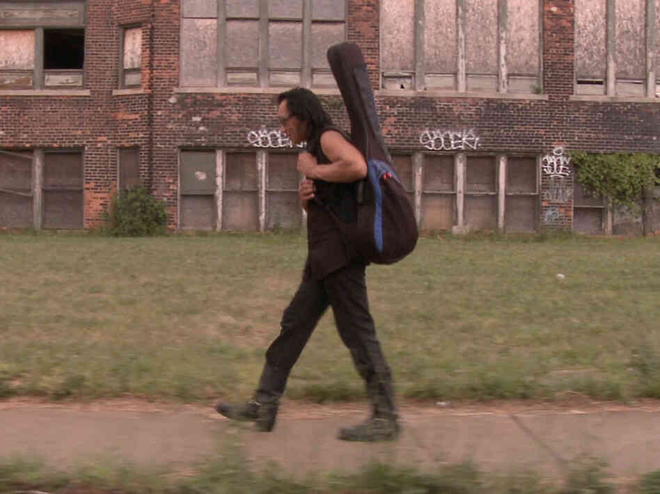 Rodriguez carries his guitar through Detroit, Mich., his hometown.