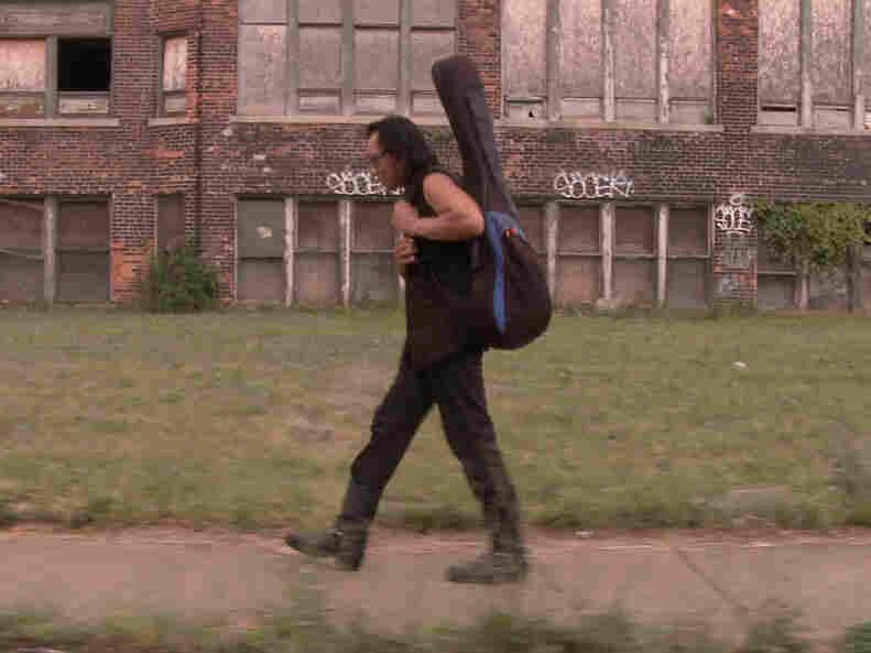 Rodriguez carries his guitar through Detroit, Mich., his hometown.