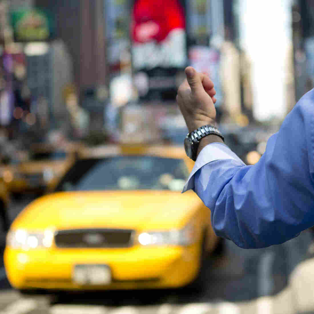 A man hails a cab in Times Square.