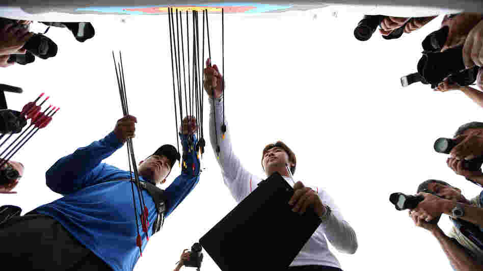 Archer Im Dong-hyun (right) of South Korea inspects his target after breaking the world record during the men's ranking round Friday.