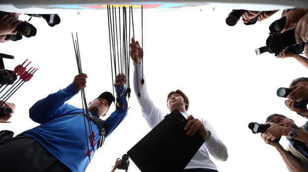 Archer Im Dong-hyun (right) of South Korea inspects his target after breaking the world record during the men's ranking round Friday. (Getty Images)