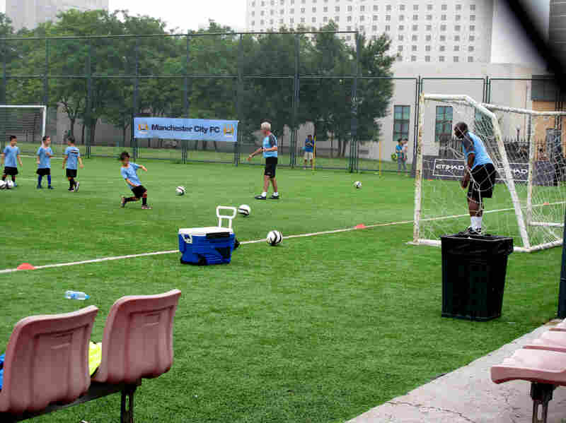 Aspiring soccer stars try to score against former Manchester City goalkeeper Alex Williams in Beijing. Local soccer clinics provide visiting international teams publicity for themselves and their sponsors.