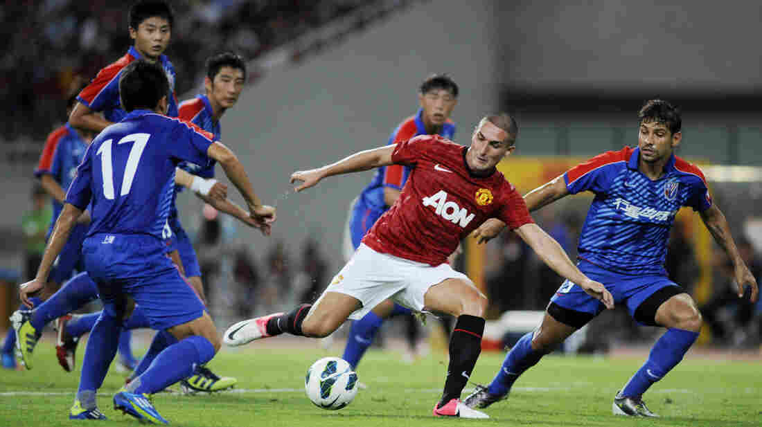 Federico Macheda of Manchester United (center) challenges players from Shanghai Shenhua during a friendly match between the two teams in Shanghai, China, on Wednesday.
