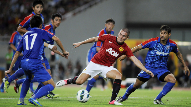 Federico Macheda of Manchester United (center) challenges players from Shanghai Shenhua during a friendly match between the two teams in Shanghai, China, on Wednesday. (Getty Images)