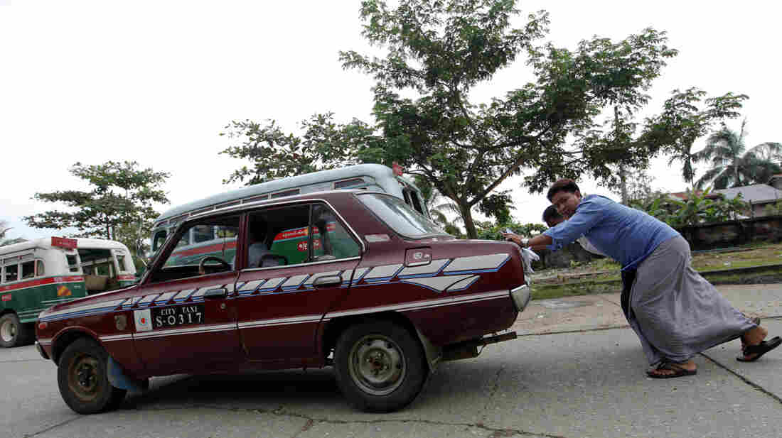 An old taxi is pushed toward a vehicle license office to be exchanged for an import permit in Yangon, Myanmar. As many Burmese citizens take cars as an investment, many imports are sold and resold with a higher markup.
