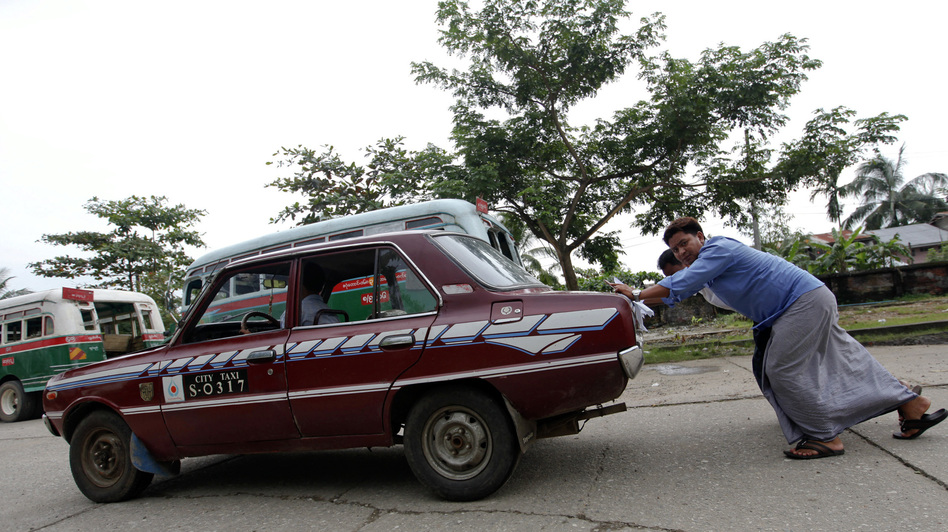 An old taxi is pushed toward a vehicle license office to be exchanged for an import permit in Yangon, Myanmar. As many Burmese citizens take cars as an investment, many imports are sold and resold with a higher markup. (Reuters/Landov)