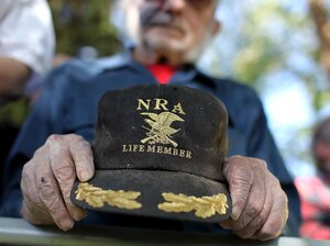 A supporter of Republican presidential candidate, Mitt Romney holds an NRA baseball cap during the singing of the National Anthem at a campaign rally at Alice Pleasant Park on May 29, 2012 in Craig, Colorado.