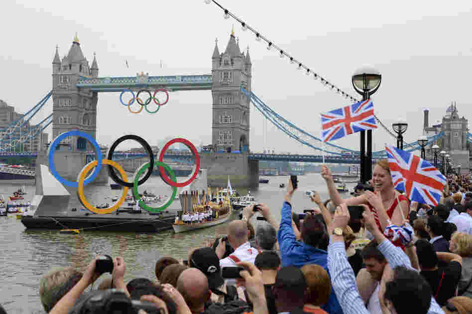 The Olympic torch is delivered by rowboat to the royal barge, Gloriana, on the River Thames, near Tower Bridge in London ahead of the opening ceremony Friday.