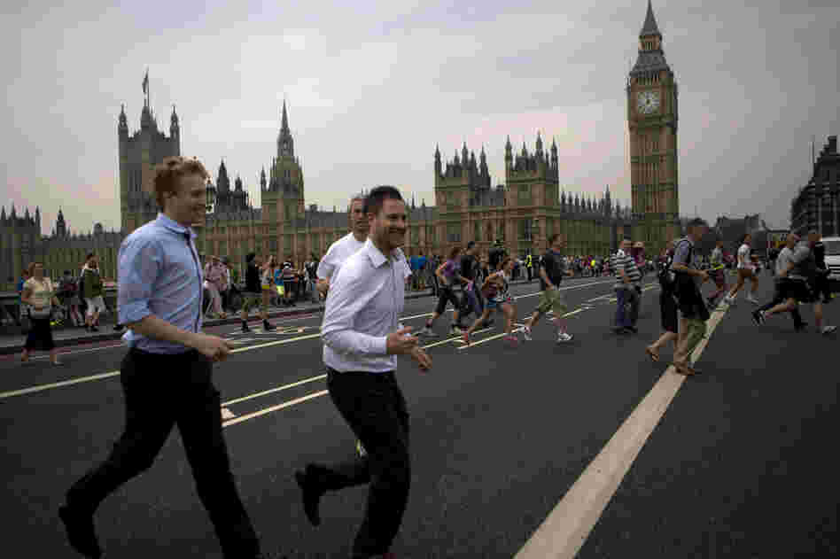 People cross the Westminster bridge to watch the Olympic flame being delivered.