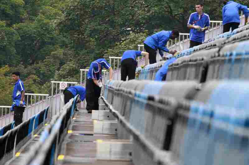 Volunteers wipe up water after a light rain at the equestrian stadium in Greenwich Park.