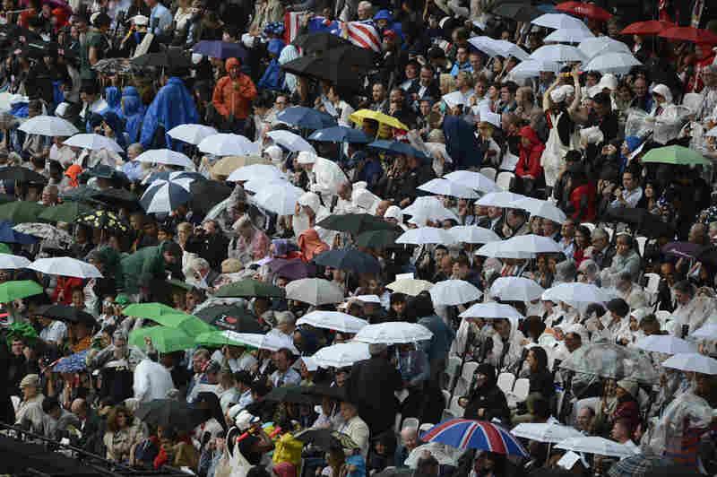 Rain falls on spectators in the Olympic stadium.