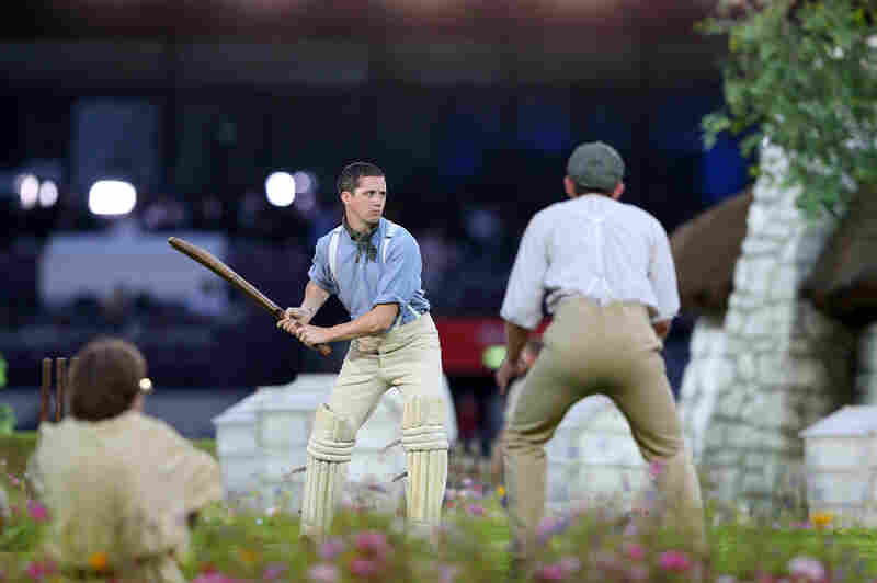 Performers depict a view of the English countryside by playing a game of cricket.