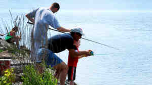 Participants in a fishing derby cast lines from a pier near Onondaga Lake's outflow in Syracuse, N.Y.
