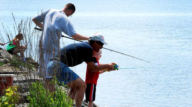 Participants in a fishing derby cast lines from a pier near Onondaga Lake's outflow in Syracuse, N.Y. (David Chanatry for NPR)