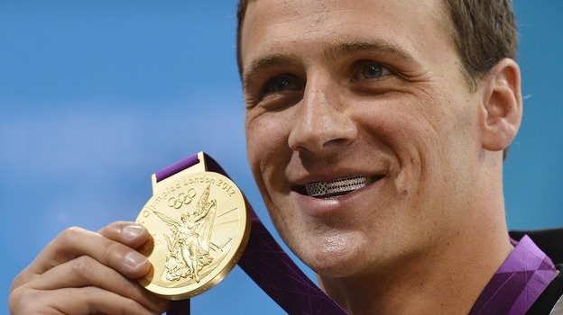Ryan Lochte smiles on the podium with his new gold medal after winning the men's 400m individual medley in London Saturday. Lochte is wearing a dental accessory known as grillz, in the shape of the American flag. (AFP/Getty Images)