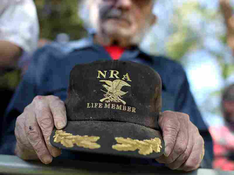A supporter of Republican presidential candidate Mitt Romney holds an NRA baseball cap during at a campaign rally in Craig, Colo., in May.