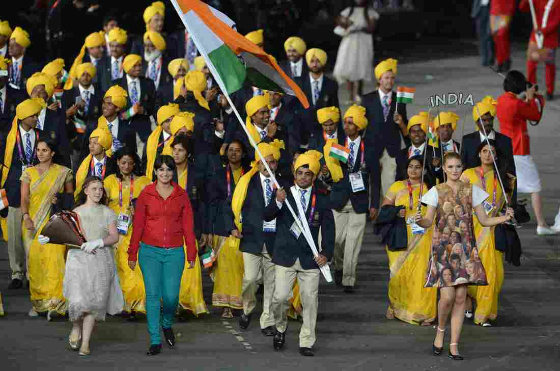 (FILES) A file picture taken on Friday shows a woman (2nd L), reportedly a student from Bangalore and an Olympic volunteer, walking next to India's flagbearer Sushil Kumar.
