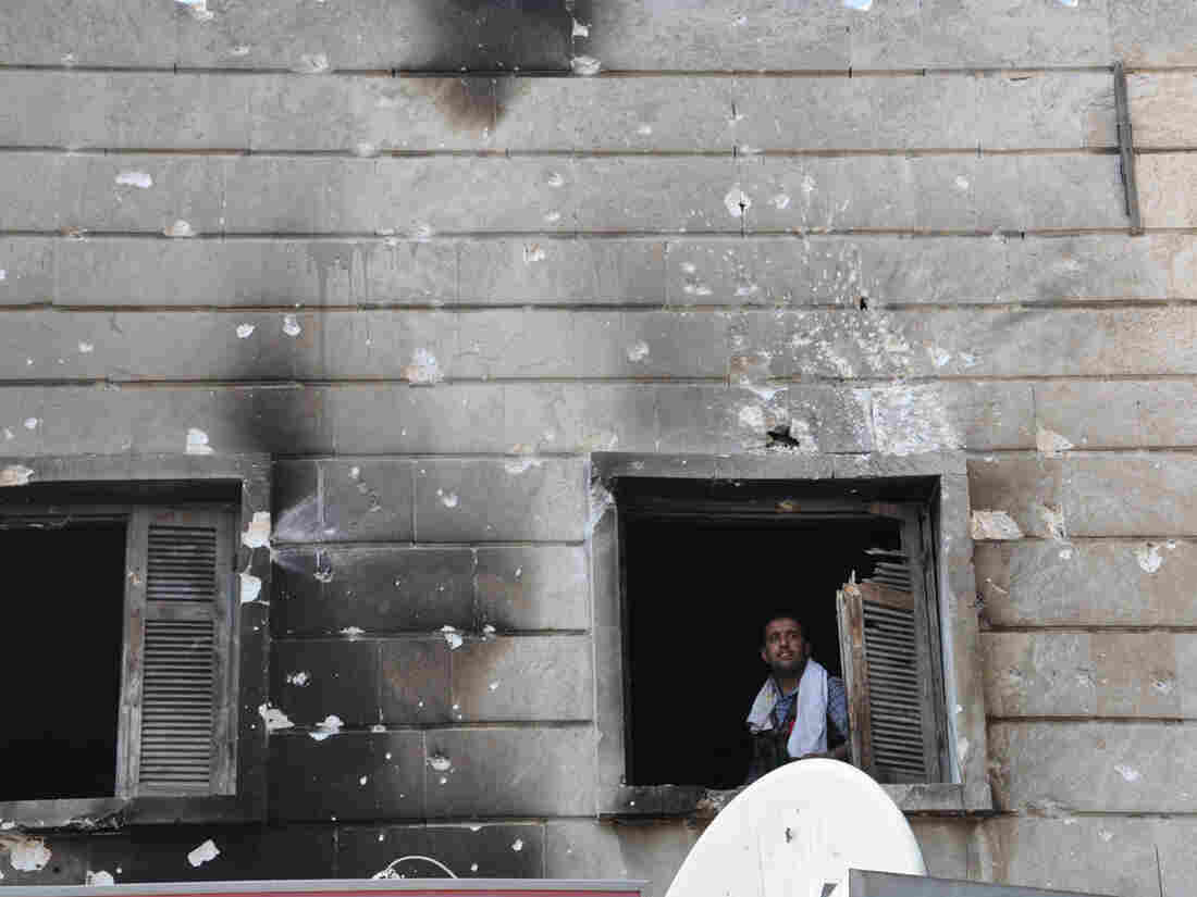 A Free Syrian Army fighter looks out from the window of a burnt-out police station in  Aleppo after it was overrun by rebel fighters last week.