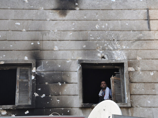 A Free Syrian Army fighter looks out from the window of a burnt-out p