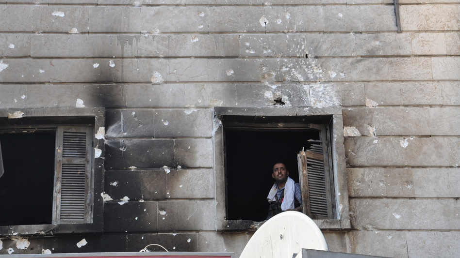 A Free Syrian Army fighter looks out from the window of a burnt-out police station in  Aleppo after it was overrun by rebel fighters last week. (AFP/Getty Images)