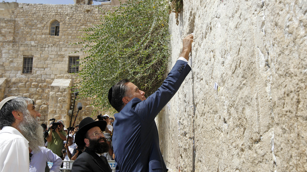Republican presidential candidate Mitt Romney places a prayer note as he visits the Western Wall in Jerusalem on Sunday. (AP)