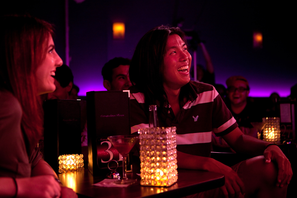 Megan Lutz, left, and Justin Chun react to Lynch's standup routine. When we laugh at a joke, Lynch hypothesizes, we are often revealing our unconscious attitudes. (NPR)
