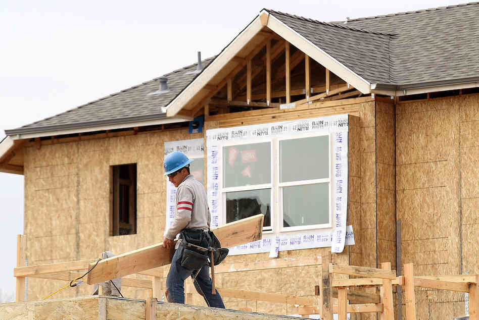 A construction worker carries lumber while working on new homes in San Mateo, Calif., in March. Homebuilding is at its highest level in nearly four years.