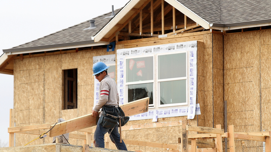 A construction worker carries lumber while working on new homes in San Mateo, Calif., in March. Homebuilding is at its highest level in nearly four years. (Getty Images)