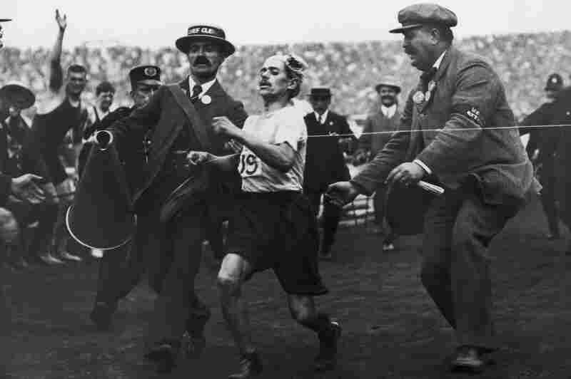 Dorando Pietri of Italy, on the verge of collapse, is helped across the finish line in the marathon. He was subsequently disqualified and the title was given to John Hayes of the United States.