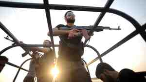 Syrian rebels patrol the streets near Aleppo, Syria.