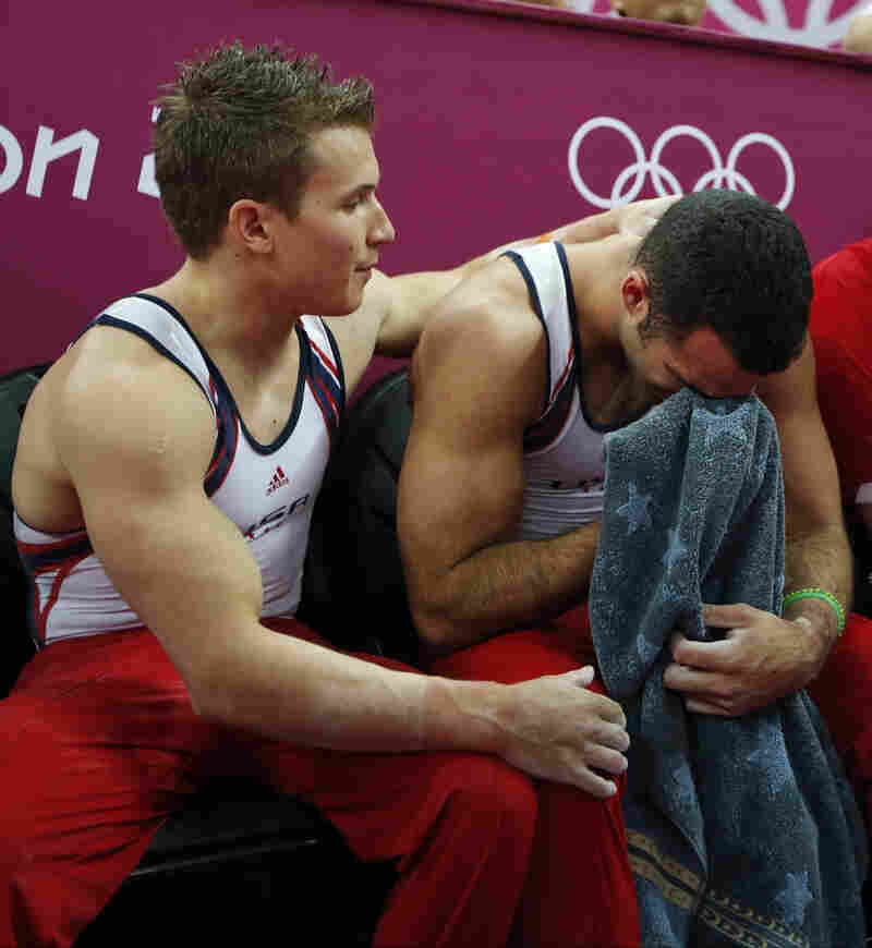 U.S. gymnast Danell Leyva (right) is comforted by teammate Jonathan Horton at the end of the artistic gymnastic men's team final.