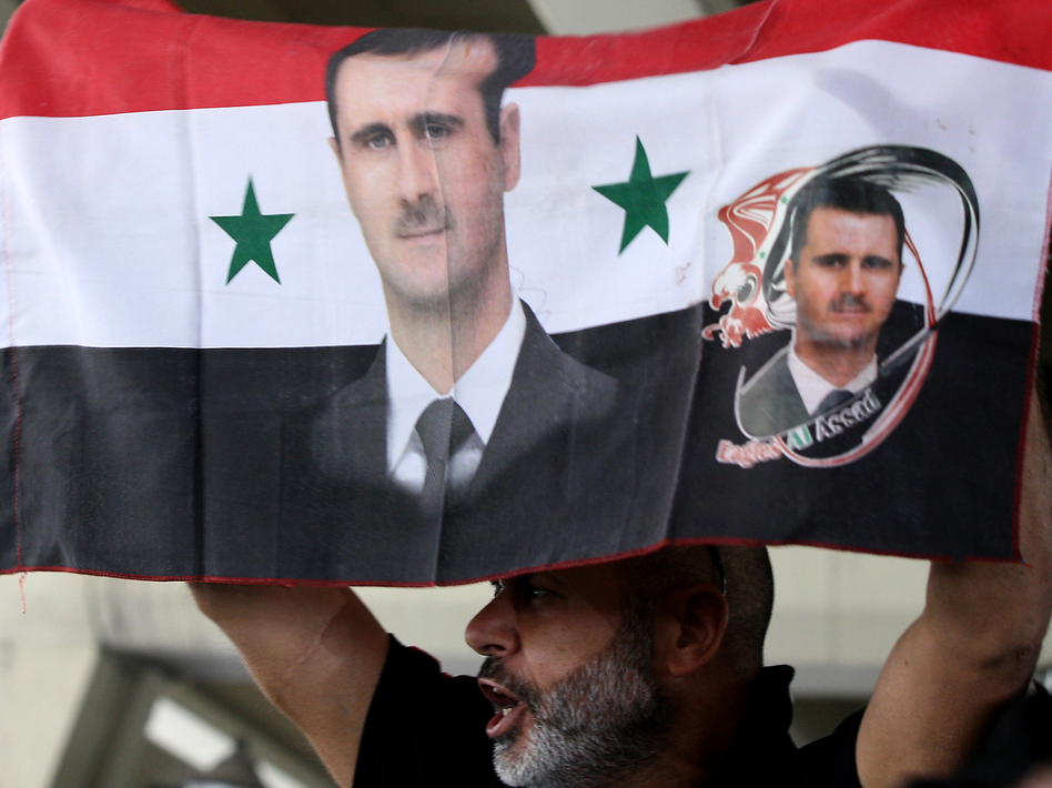 A Syrian man holds a national flag bearing pictures of President Bashar Assad during a pro-regime protest to condemn a deadly attack in the central Midan district of Damascus on April 27. (AFP/Getty Images)