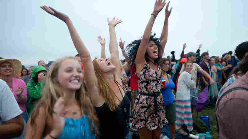 Fans, from left, Jenn Spofford, Chrissy Stewart and Suzanna Kopec, all of Providence, R.I., cheer for My Morning Jacket as the band performs on the Fort Stage at the Newport Folk Festival.